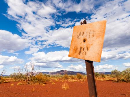 een oud roestig blikken bord in het binnenland van West-Australië, tegen een levendige blauwe lucht en een oranje woestijnachtige achtergrond. Stockfoto