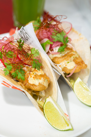 Golden fried cod fish taco served with parsley, red onion hollandaise sauce, and a fresh wedge of lime. Stock Photo