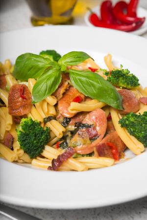 Een heerlijke verse gastronomische Italiaanse strozzapreti pastagerecht, met pancetta, Italiaanse worst, broccoli, groenten, gegarneerd met verse basilicum. Stockfoto