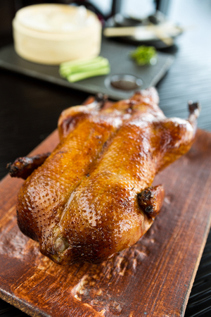 A beautiful roasted, free range, crispy golden oriental peking duck, served on a rustic wooden cutting board, ready to be sliced. Imagens