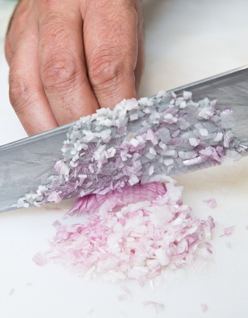 A knife dicing fresh organic Shallots, on a white cutting board.