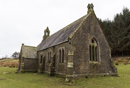 An creepy old abandoned christian church, on a gloomy overcast day, covered in moss, deep in the english countryside.