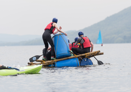 Lake Coniston, England, 06062016, A group of men on a makeshift raft, on Lake Coniston, The Lake District. Team building exercise. Editorial