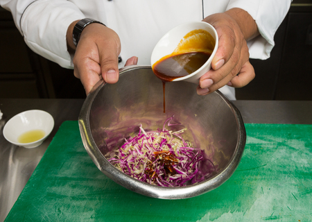 spicy barbecue sauce being poured and mixed, into a bowl, of freshly prepared homemade coleslaw.
