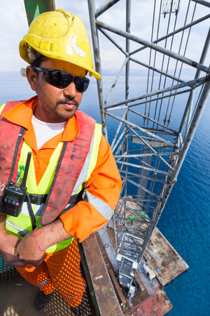 Aqaba, Jordan, 10102015, A construction worker in hi visibility jacket, safety helmet and sunglasses, high up in a crane above the dead sea, looking over the port construction site.