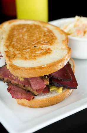 Smoked meat beef sandwich with mustard and black pepper corns, served on a plate with coleslaw.