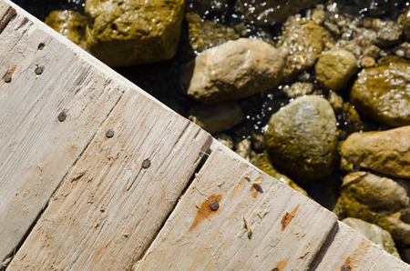 A close up of an old wooden jetty texture with rocks and sea below. Stock Photo