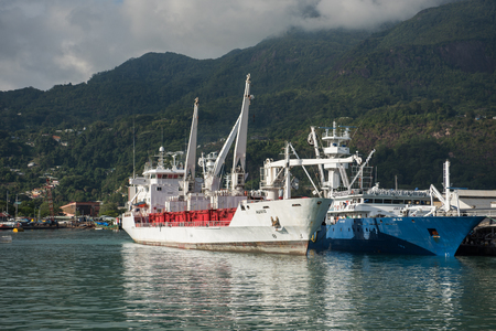 make, seychelles, 05052017 Cargo boats importing and exporting good in the seychelles, at the port in Mahe. The picture perfect mountain scenery in the tropical island is the backdrop of the moored boats. Editorial