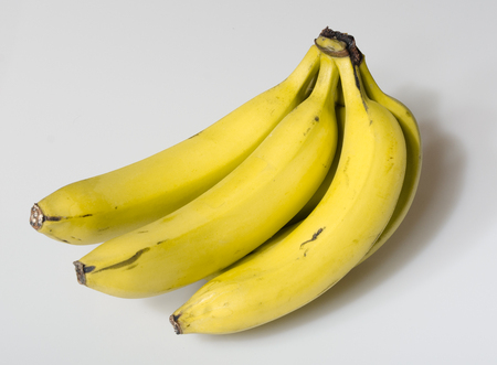 A beautiful bright yellow bunch of ripe bananas isolated on a white studio background. healthy vivid colours. Stock Photo