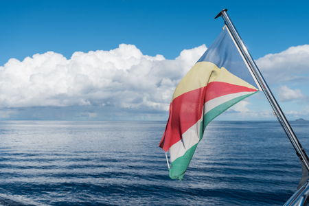 A rustic weathered seychelles flag blowing in the wind against a vivid blue and silver ocean seascape view from a tourist boat. Breath taking and refreshing.