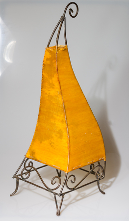 traditional iron and goat hide warm yellow moroccan goat skin lamp photographed and isolated on a white plain background, with a beautiful shadow. Beautiful decorative iron work. Stock Photo