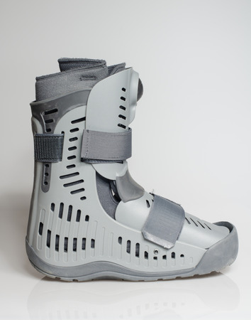 A orthopaedic grey plastic boot ankle brace injury protecting boot, with straps isolated on a white background. Broken feet broken foot protection. Stock Photo