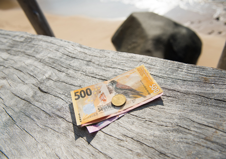 make, seychelles, 05052017, Seychelles rupees on a rustic wooden warm sunny background. Rupees are the money currency in mahe. Cash and bank notes.