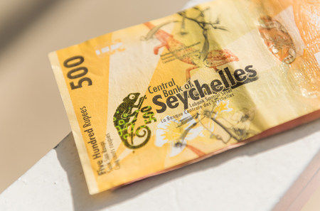 Seychelles rupees on a rustic wooden warm sunny background. Rupees are the money currency in mahe. Cash and bank notes.