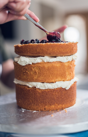 A beautiful organic delicious orange warm baked sponge cake, with fresh cream inside, with blackcurrant jam being spread on the top.