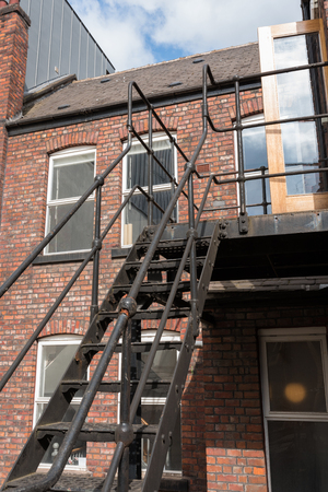 urban new york  style metal vintage steel fire escape ladder stairs in manchester england. Fire escape route on the side of a building saves lives. Editorial