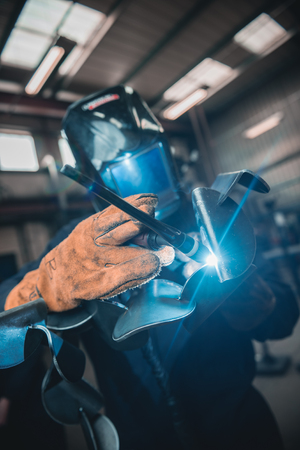 london, england, 02/02/2018 A vibrant action shot of a skilled working metal welder in action, welding metal. Photographed with a slow shutter speed and spark trails. Orange and teal. Redactioneel