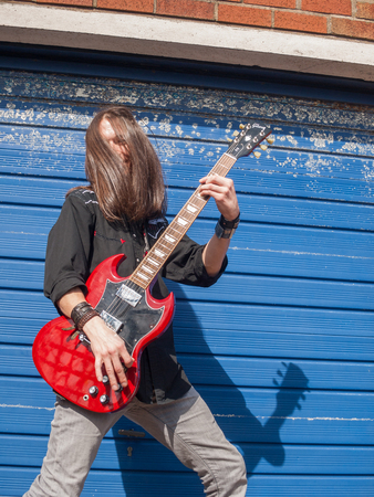 london, england, 04042018 A rock and roll heavy metal concert guitarist with long hair rocking out playing a red lead guitar on the street against closed shutters on a high street. Busking street art entertainment.