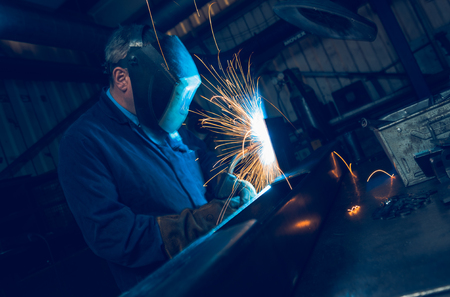 A vibrant action shot of a skilled working metal welder in action, welding metal. Photographed with a slow shutter speed and spark trails. Orange and teal. Imagens