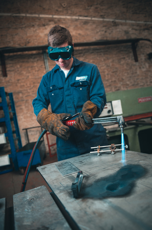 london, england, 02022018 A vibrant action shot of a skilled working metal welder in action, welding metal. Photographed with a slow shutter speed and spark trails. Orange and teal. Editorial