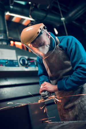 london, england, 02022018, Young industrial metal working apprentice worker angle griding,learning various metal working skills in an industrial factory setting. Apprentice schemes returning to england.