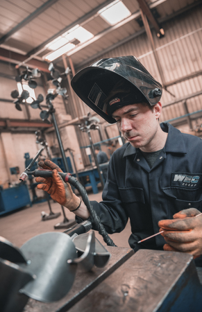 london, england, 02022018, Young industrial metal working apprentice worker learning various metal working skills in an industrial factory setting. Apprentice schemes returning to england.