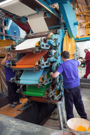 lancashire, england, 05/05.2017 An industrial wallpaper and paint factory with giant industrial wall paper rolling machines in various colours. orange, white,blue and green paint being mixed.
