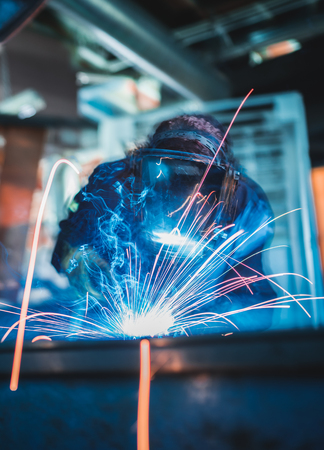 A vibrant action shot of a skilled working metal welder in action, welding metal. Photographed with a slow shutter speed and spark trails. Orange and teal fashionable colour palette.
