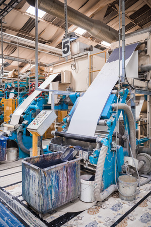 An empty quiet industrial wallpaper and paint factory with giant industrial paint rolling machines, printing white wallpaper.