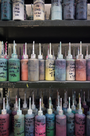 A shelf of Industrial fabric and wallpaper dye ink paint, in plastic bottles with nozzles. Fabric dye is used in creating colour for the clothing and textile industry. fashion industry. Muted colours. 스톡 콘텐츠