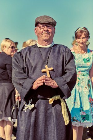 london, England, 05/05/2017, A stylish retro vintage fashionable fake priest pastor man of the lord with praying hands and flatcap at a vintage event..