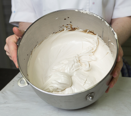A beautiful rich and creamy , white whipped meringue mixture in a large metal mixing bowl.