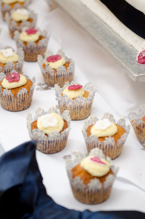 Beautiful inviting Sponge and cream cup cakes with a shallow depth of field, photographed on a table.
