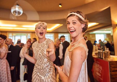 10/10/2018 Londres, Inglaterra, Vintage retro Great Gatsby Girls bailando en formación, retroceso retro bailando, chicas nostálgicas. edificio art deco.