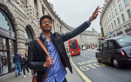 05052017 A young arabic male tourist in london hailing a taxi cab on the world famous high streets. Urban cosmopolitan city living.