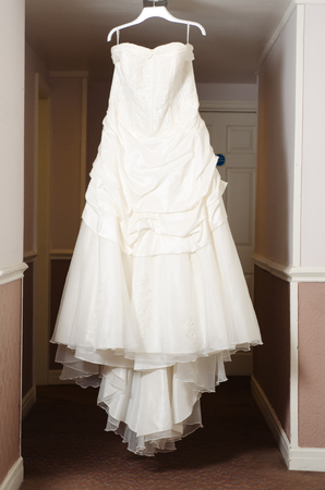 A beautiful cream and clean Wedding dress Hanging in the hall of a hotel room. Wedding love fashion and celebration.