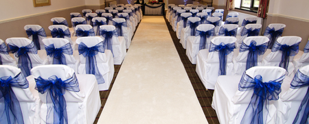 gorgeous intricate wedding ceremony chair bow details on empty chairs in preparation for wedding ceremony.