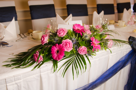 An empty blank paper table card name plate sign on a wedding table, with beautiful pink flowers shot with a shallow depth of field. perfect for placing names in composite designs.