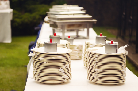 A stack of empty clean white buffet banquet crockery plates on a whit stable at an outdoor event in summer. bbq wedding self service eating methods. Stock fotó