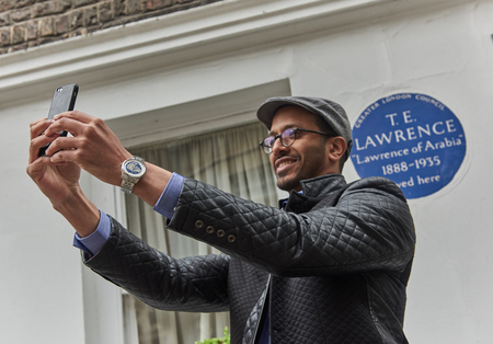 london, england, 05/05/2018 A male tourist taking selfie photos with his mobile phone outside the world famous london landmark lawrence of arabia house. Editorial