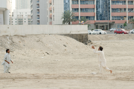 15/05/2017 Tecom, Dubai, Pakistani immigrant workers workforce relaxing and taking time to play some volleyball on the dusty construction site grounds. Dubai workers fining time to play sport.