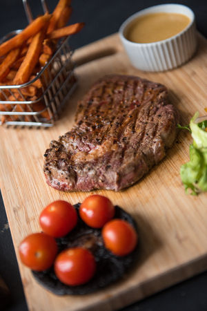 A platter of sirloin steak, salad, fries, sauce, tomato and mushrooms, served on a rustic wooden cutting board. Dark food photography with a mechanics workshop industrial setting.