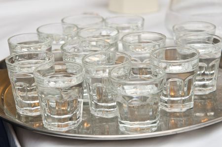 A metal silver tray full of all shot glasses of vodka, gin and tequila clear pure alcohol. party and celebrations. Drink alcohol responsibly.