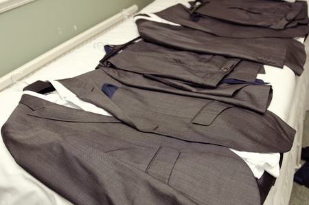 A set of fashionable best mens grey wedding suits, suit tops and trousers, laid out ready for the groomsmen to get changed into. getting ready at a wedding celebration. Stockfoto