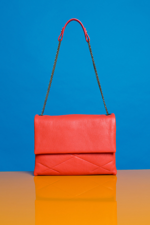 A beautiful expensive womans orange leather handbag, against a complimentary blue coloured background with the bag strap floating in the air.