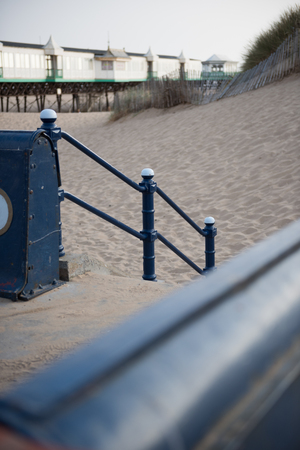 A rustic metal seaside bannister railing against a sandy beach backdrop. railings saves lives at the seaside. vintage seaside architecture.