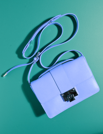 A beautiful expensive womans blue leather handbag against a complimentary green coloured background with the bag strap floating in the air. creative product photography. Reklamní fotografie