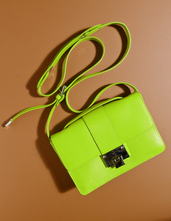 A beautiful expensive womans green leather handbag against a complimentary orange coloured background with the bag strap floating in the air. creative product photography.