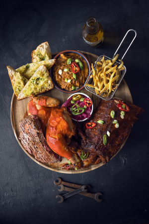 london, england, 05/05/2018 A beautiful delicious golden rack of meaty bbq pork ribs, bbq chicken thigh, french fries in a metal frying basket, , chilli and salad, served on a fashionable grey slate 版權商用圖片