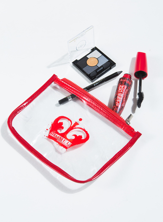 london, england, 05052019 A clear plastic rimmel make up bag, with various cosmetics being emptied onto a plain white background. beauty and glamour products in a studio setting.
